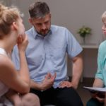 Group of adults speaks with social worker
